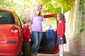 Mother driving to school with children passing daughter bag smiling at each other Stock Image