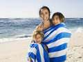 Mother and daughter (5-7) wrapped in towel on beach, smiling, portrait of girl