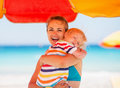 Mother embracing baby on beach under umbrella Royalty Free Stock Photo