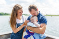 Mother and father with baby son standing on pier by the river Royalty Free Stock Photo