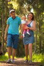 Mother, father and baby walking in the park. Royalty Free Stock Photo