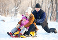 Mother father and child in a winter park family walking parents with on sled Royalty Free Stock Photo