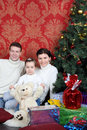 Mother father and daugther sit near christmas tree on floor with gifts at home Stock Photos