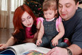Mother, father and little daughter reads book Royalty Free Stock Photo