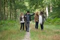 Mother and father walking with daughters in the forest portrait of a Stock Photography