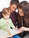 Mother, fathher and little daughter reading book Royalty Free Stock Photography