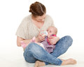 Mother feeding baby from bottle young on a white background happy family Royalty Free Stock Images