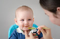 Mother feeding beautiful baby boy with a spoon blonde hair blue eyes and dirty face the cute infant is eating his meal and Royalty Free Stock Images