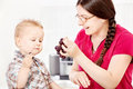 Mother feeding child with grape son grapes in kitchen Stock Images