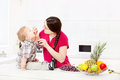 Mother feeding child in kitchen with grapes Royalty Free Stock Images