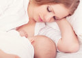 Mother feeding her baby in the bed. sleeping together