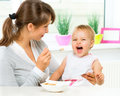 Mother feeding her baby girl with a spoon Royalty Free Stock Photos