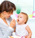 Mother feeding her baby girl with a spoon Royalty Free Stock Photography