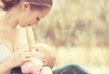 Mother feeding her baby in nature outdoors in the park Royalty Free Stock Photo
