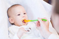 Mother feeding her lovely smiling baby boy with spoon Royalty Free Stock Photo