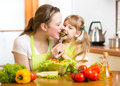 Mother feeding kid vegetables in kitchen girl Royalty Free Stock Images