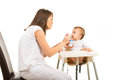 Mother feeding toddler boy with yogurt against white background Royalty Free Stock Images