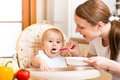 Mother feeds baby mom with spoon Stock Photography