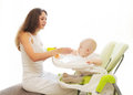 Mother feeds baby spoon sitting for table home at Royalty Free Stock Images
