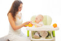 Mother feeds little baby spoon on table home at Stock Photos