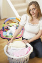 Mother Folding Baby Clothes At Home Royalty Free Stock Photography