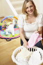 Mother Folding Baby Clothes At Home Stock Photography