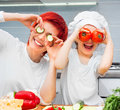 Mother and funny daughter playing in the kitchen with vegetables Stock Photography