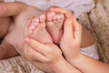 Mother gently hold baby leg in hand. Royalty Free Stock Photo