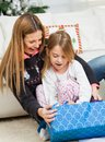 Mother and girl opening christmas present happy together at home Royalty Free Stock Photos