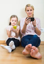 Mother and girl playing with mobile phones indoor Royalty Free Stock Photo