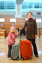 Mother and girl with suitcases standing at airport Stock Photos