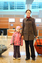 Mother and girl with suitcases standing at airport Royalty Free Stock Photography
