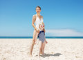 Mother and girl in swimsuits at sandy beach on a sunny day Royalty Free Stock Photo
