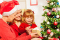Mother and grandmother giving present to daughter family with little three years old girl sitting near christmas tree opening new Stock Photos
