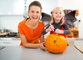 Mother with halloween dressed daughter creating jack o lantern сheerful big orange pumpkin in decorated kitchen traditional Royalty Free Stock Photography