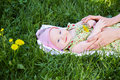 Mother hands touch her baby lies grass Royalty Free Stock Photography