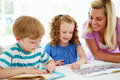 Mother helping children with homework in kitchen looking at textbook smiling Royalty Free Stock Images