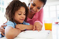 Mother helping daughter with homework in kitchen pointing to textbook looking over shoulder Royalty Free Stock Photography