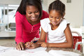 Mother helping daughter with homework in kitchen smiling Royalty Free Stock Photography