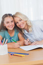 Mother helping daughter with homework in living room Royalty Free Stock Photo
