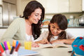 Mother helping daughter with reading homework at table sitting down in kitchen Royalty Free Stock Image