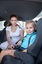 Mother helping daughter to fasten car safety belt in restraint seat Stock Photo