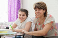 Mother helping her child with homework adult women to teenager to learn lessons at home Stock Images