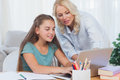 Mother helping her daughter to do homework with a laptop Royalty Free Stock Photography