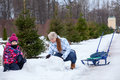 Mother helping her daughter to make a snowman in winter street Stock Photo