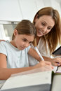 Mother helping her daughter writing homework mom with Royalty Free Stock Photos