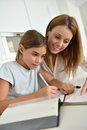 Mother helping her daughter writing homework mom with Royalty Free Stock Photography