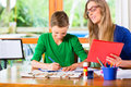 Mother helping son with homework assignment painting a picture Royalty Free Stock Images
