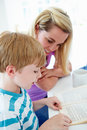 Mother helping son with homework in kitchen close up of sitting at table Stock Photo