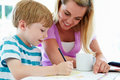 Mother helping son with homework in kitchen pointing to book smiling Royalty Free Stock Photos